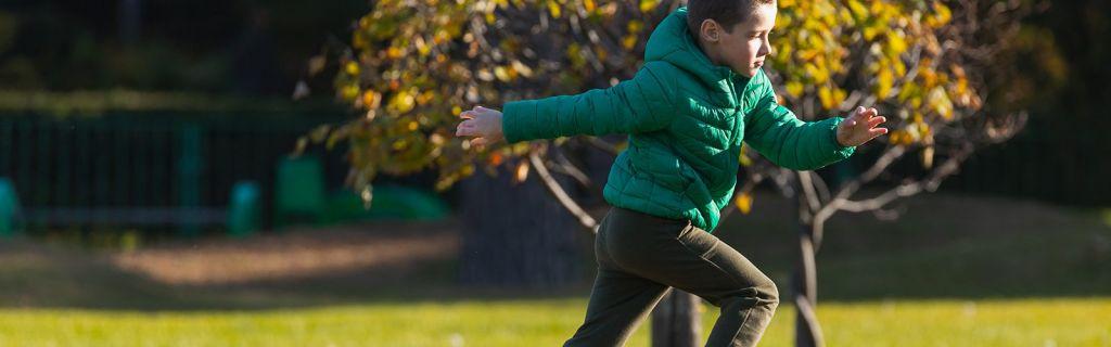Kid running over green grass