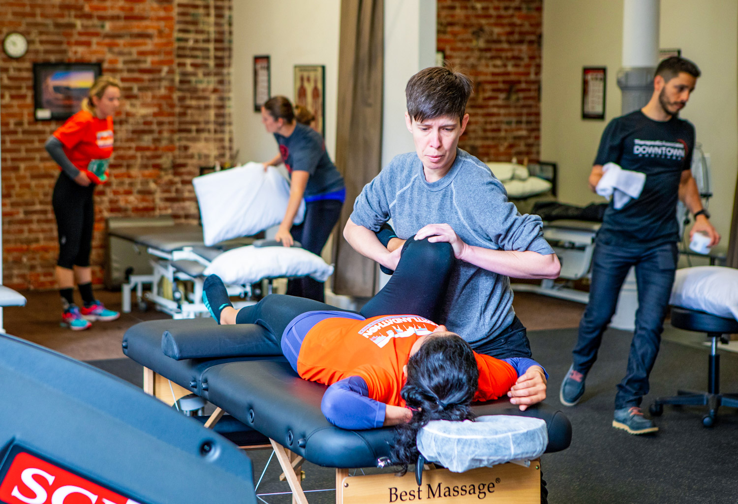 Chiropractor giving massage to a patient lying on a bed
