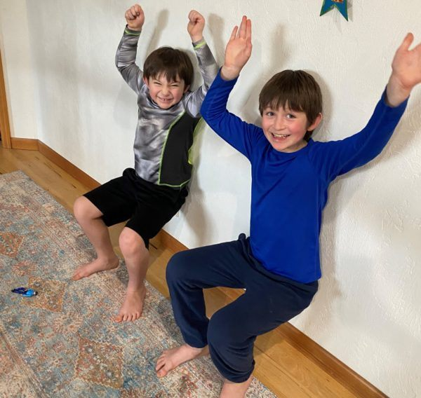 Two kids doing wall sits