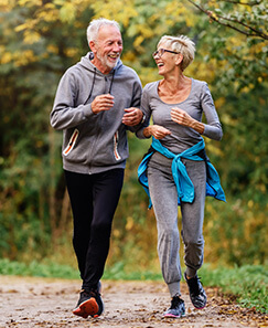 Older couple walking outdoors laughing