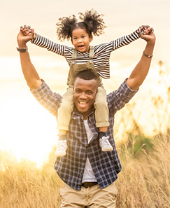 Daughter on fathers shoulders in open field
