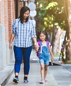 A woman and a little girl walking holding hands