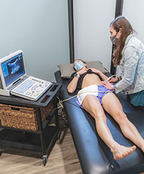 Physical therapist performs ultrasound imaging on patient